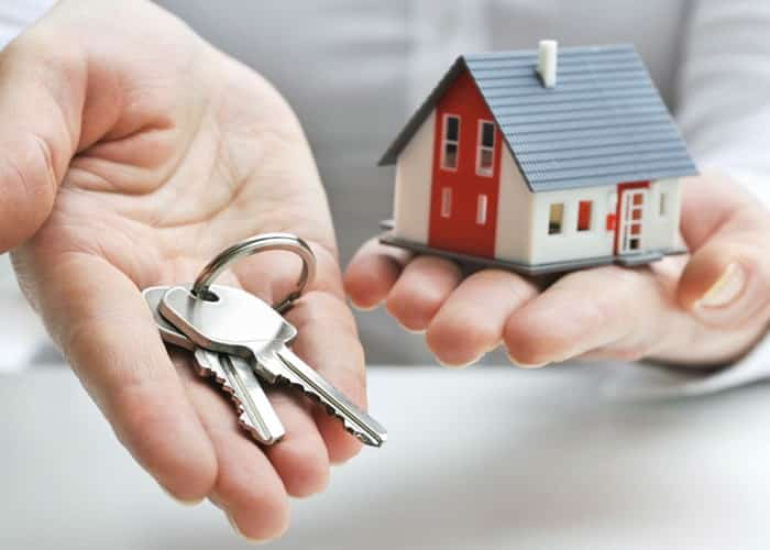One hand holding keys and one hand holding a little house for transfer of property ownership