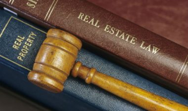 A brown book with real estate law on spine next to blue book with real property on the spine. A wooden gavel lays on top for Real Estate Law