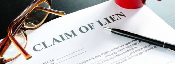 A claim of lien document lays on a table with brown glasses to the left and a black pen to the right for Lien Release