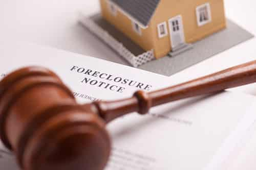 A small peach colored house in the background on a white table. A foreclosure notice lays on the table with a wooden gavel on top for Foreclosure Service