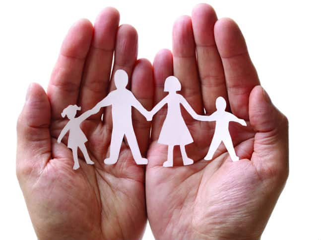 A pair of hands palm side up hold a little paper cutout of a family for Setting up a Trust